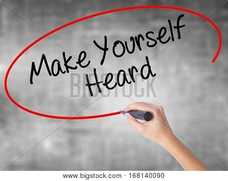 Woman Hand Writing Make Yourself Heard With Black Marker Over Transparent Board