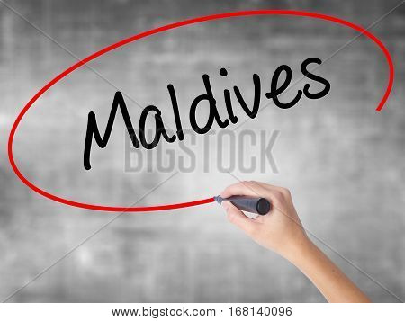 Woman Hand Writing Maldives  With Black Marker Over Transparent Board