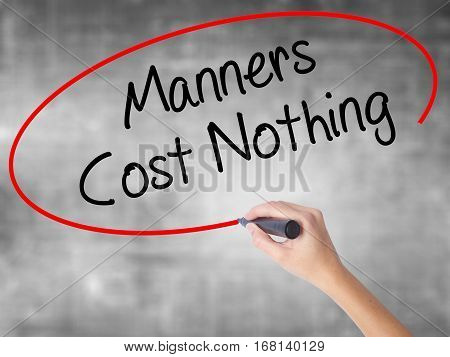 Woman Hand Writing Manners Cost Nothing With Black Marker Over Transparent Board