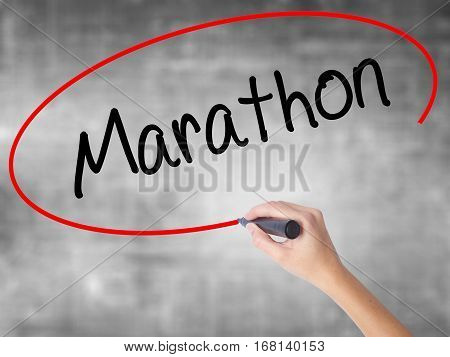 Woman Hand Writing Marathon With Black Marker Over Transparent Board.