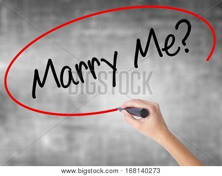 Woman Hand Writing Marry Me? With Black Marker Over Transparent Board.