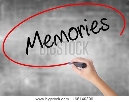 Woman Hand Writing Memories With Black Marker Over Transparent Board