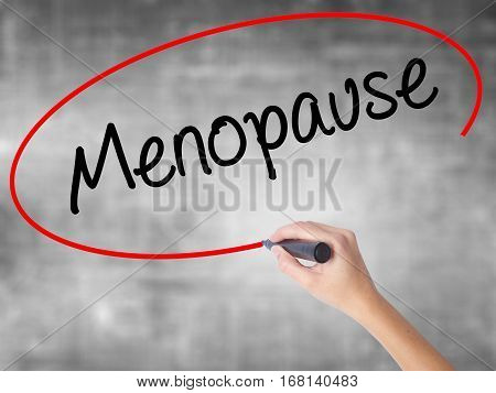 Woman Hand Writing Menopause With Black Marker Over Transparent Board.