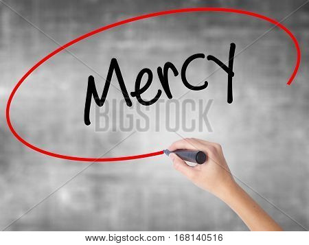 Woman Hand Writing Mercy With Black Marker Over Transparent Board