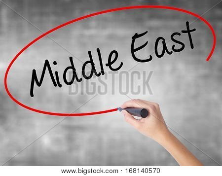 Woman Hand Writing Middle East With Black Marker Over Transparent Board