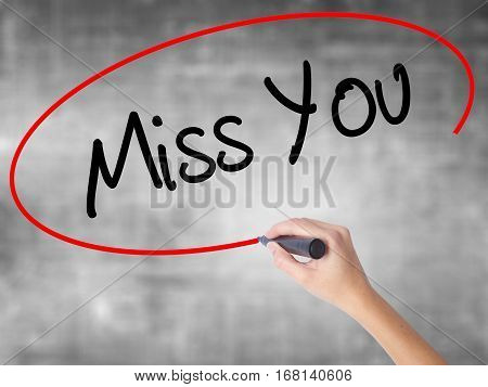 Woman Hand Writing Miss You With Black Marker Over Transparent Board