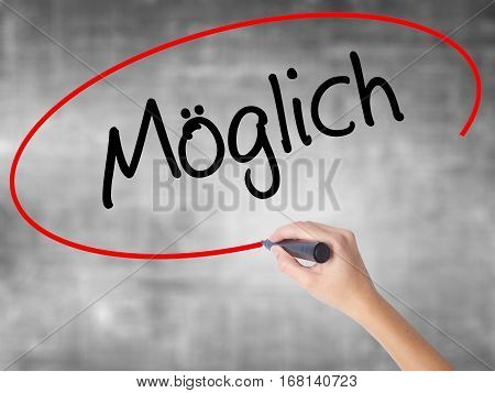 Woman Hand Writing Moglich (possible In German) With Black Marker Over Transparent Board.