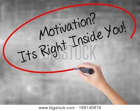 Woman Hand Writing Motivation? Its Right Inside You!  With Black Marker Over Transparent Board