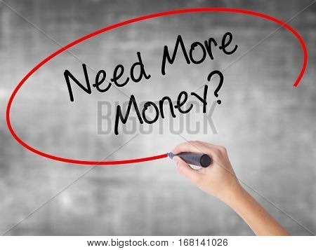 Woman Hand Writing Need More Money? With Black Marker Over Transparent Board