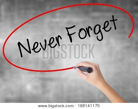 Woman Hand Writing Never Forget  With Black Marker Over Transparent Board