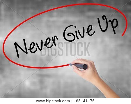 Woman Hand Writing Never Give Up With Black Marker Over Transparent Board