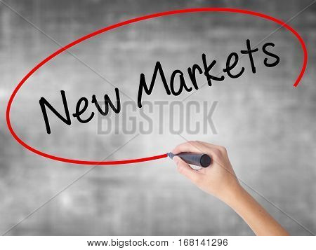 Woman Hand Writing New Markets With Black Marker Over Transparent Board