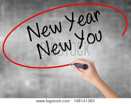 Woman Hand Writing New Year New You With Black Marker Over Transparent Board