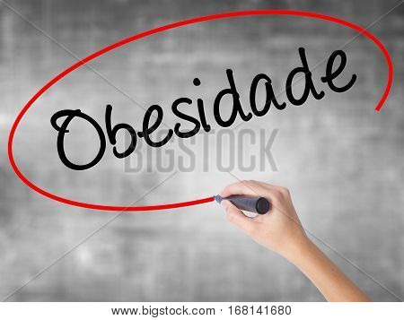 Woman Hand Writing Obesidade (obesity In Portuguese)  With Black Marker Over Transparent Board