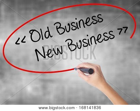 Woman Hand Writing Old Business - New Business With Black Marker Over Transparent Board