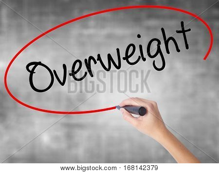 Woman Hand Writing Overweight  With Black Marker Over Transparent Board