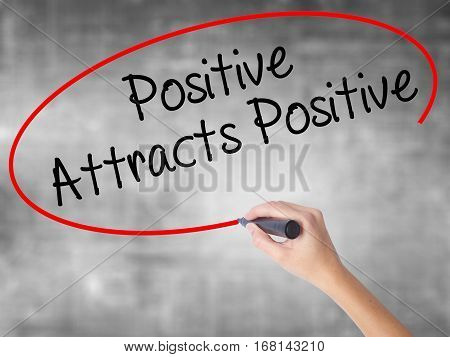 Woman Hand Writing Positive Attracts Positive With Black Marker Over Transparent Board