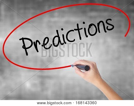 Woman Hand Writing Predictions  With Black Marker Over Transparent Board