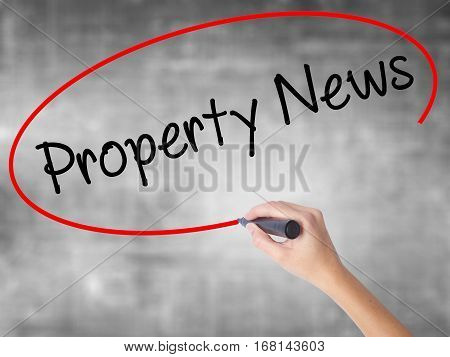 Woman Hand Writing Property News With Black Marker Over Transparent Board.