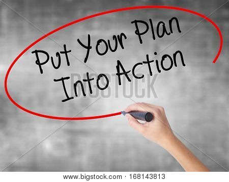 Woman Hand Writing Put Your Plan Into Action With Black Marker Over Transparent Board