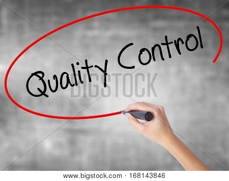 Woman Hand Writing Quality Control With Black Marker Over Transparent Board