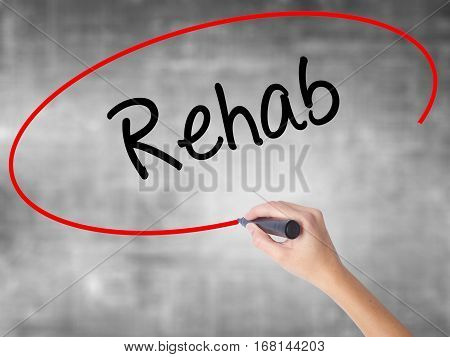 Woman Hand Writing Rehab With Black Marker Over Transparent Board