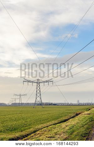 Power pylons and high voltage lines in an agricultural landscape in the Netherlands. In the background the contours of a cooling tower of a power plant and chimneys are visible. It is a cloudy day in the winter season.