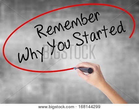 Woman Hand Writing Remember Why You Started With Black Marker Over Transparent Board