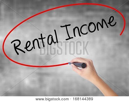 Woman Hand Writing Rental Income With Black Marker Over Transparent Board.