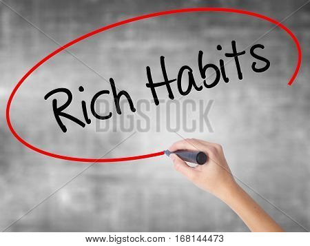 Woman Hand Writing Rich Habits With Black Marker Over Transparent Board