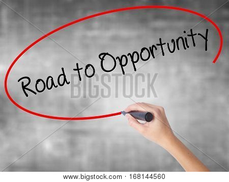 Woman Hand Writing Road To Opportunity With Black Marker Over Transparent Board