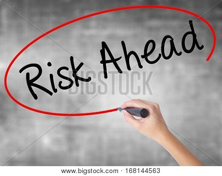 Woman Hand Writing Risk Ahead With Black Marker Over Transparent Board