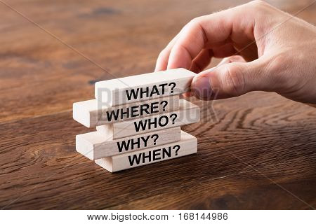 Person Arranging A Set Of Questions On Wooden Block At Wooden Desk