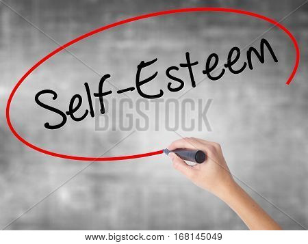 Woman Hand Writing Self-esteem With Black Marker Over Transparent Board.