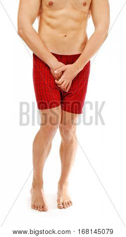 Medical concept. Closeup of man in red boxers with health problem on white background