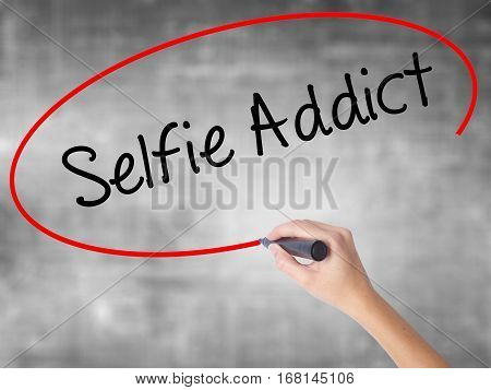 Woman Hand Writing Selfie Addict With Black Marker Over Transparent Board