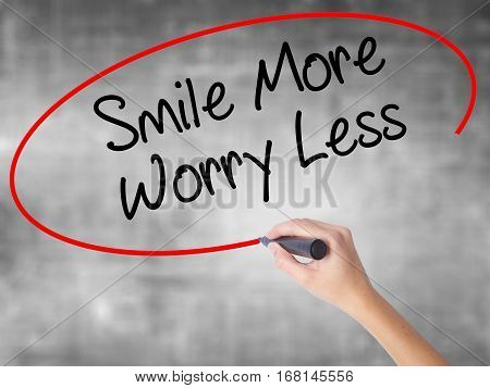 Woman Hand Writing Smile More Worry Less With Black Marker Over Transparent Board