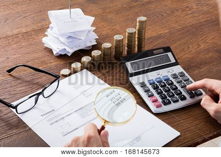 Auditor Hand Checking Invoice Using Magnifying Grass. Tax Fraud Investigation Concept