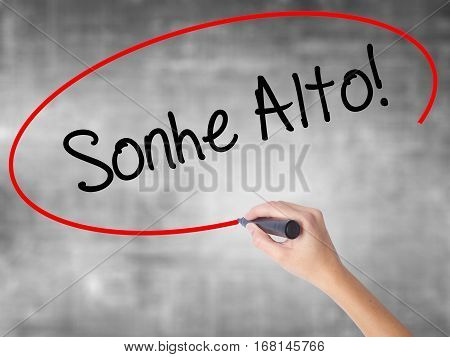 Woman Hand Writing Sonhe Alto! (dream Big In Portuguese) With Black Marker Over Transparent Board