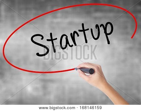 Woman Hand Writing Startup  With Black Marker Over Transparent Board