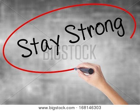 Woman Hand Writing Stay Strong With Black Marker Over Transparent Board.