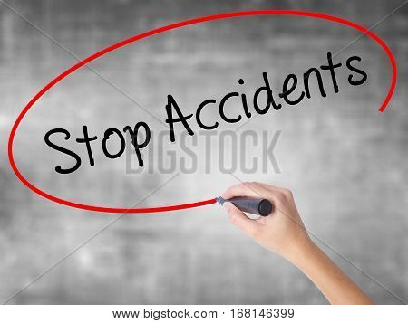 Woman Hand Writing Stop Accidents With Black Marker Over Transparent Board