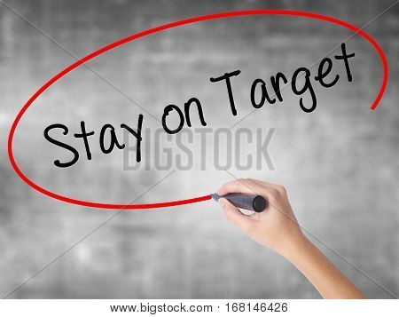 Woman Hand Writing Stay On Target With Black Marker Over Transparent Board.