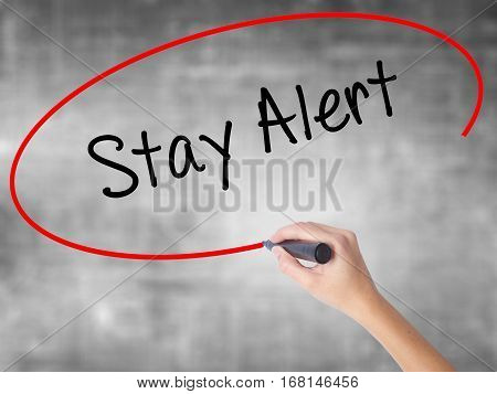 Woman Hand Writing Stay Alert With Black Marker Over Transparent Board