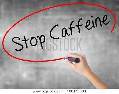 Woman Hand Writing Stop Caffeine With Black Marker Over Transparent Board