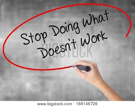 Woman Hand Writing Stop Doing What Doesn't Work With Black Marker Over Transparent Board
