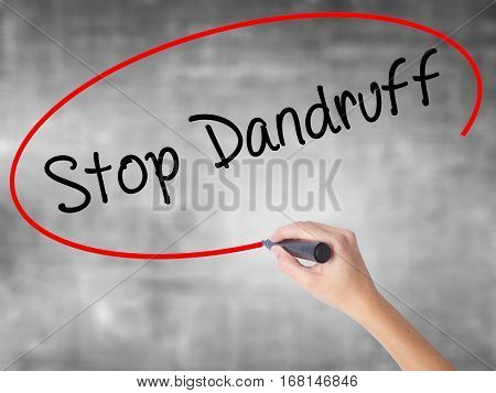Woman Hand Writing Stop Dandruff With Black Marker Over Transparent Board