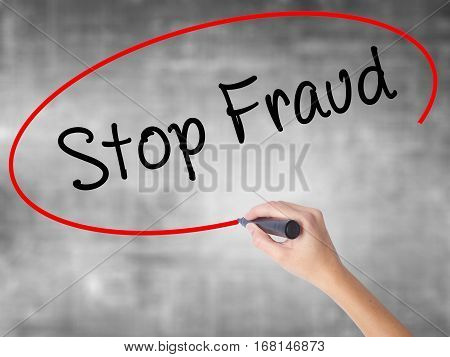 Woman Hand Writing  Stop Fraud  With Black Marker Over Transparent Board