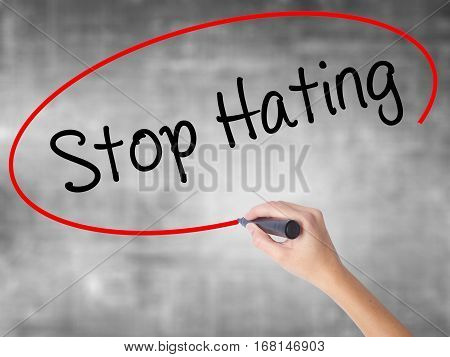 Woman Hand Writing Stop Hating  With Black Marker Over Transparent Board