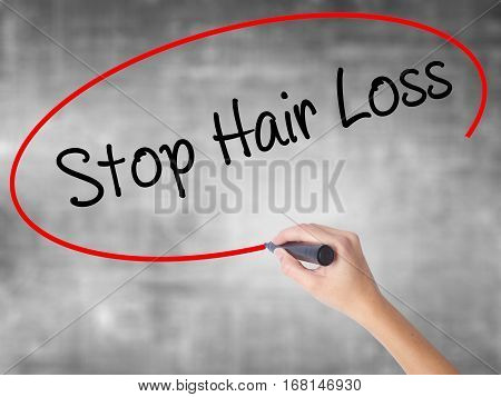Woman Hand Writing Stop Hair Loss  With Black Marker Over Transparent Board